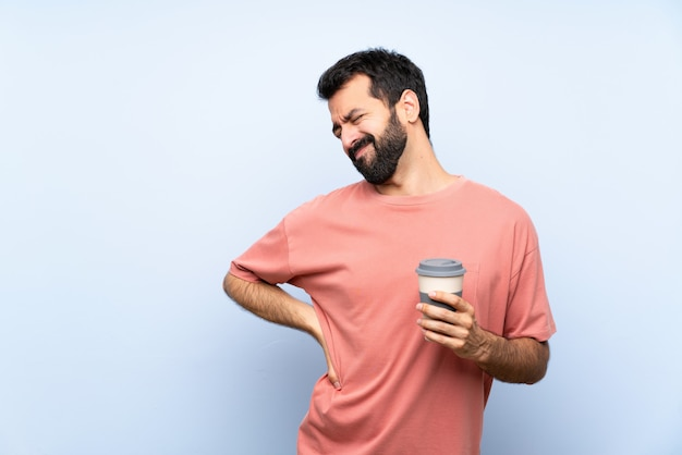 Joven con barba sosteniendo un café para llevar sobre la pared azul aislada que sufre de dolor de espalda