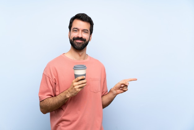 Joven con barba sosteniendo un café para llevar sobre la pared azul aislado apuntando con el dedo hacia el lado