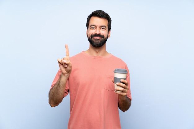 Joven con barba sosteniendo un café para llevar sobre pared azul aislado mostrando y levantando un dedo en señal de lo mejor