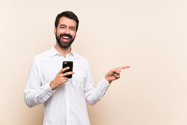 Joven con barba sosteniendo un móvil apuntando hacia un lado para presentar un producto
