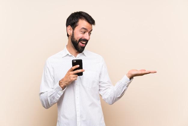 Joven con barba sosteniendo un móvil con copyspace con dos manos