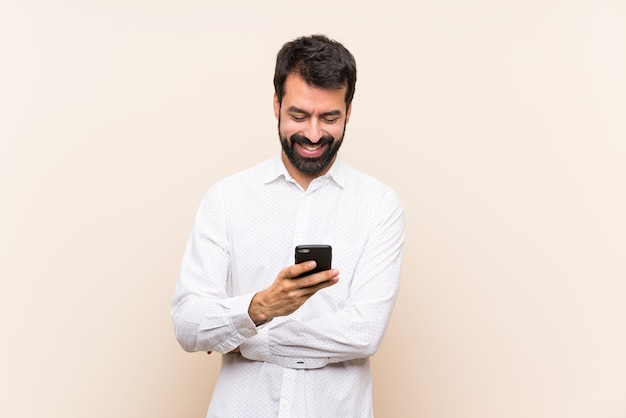 Joven con barba sosteniendo un móvil enviando un mensaje con el móvil