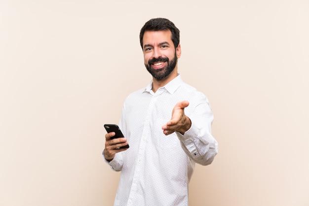Joven con barba sosteniendo un móvil estrechándole la mano para cerrar un buen trato