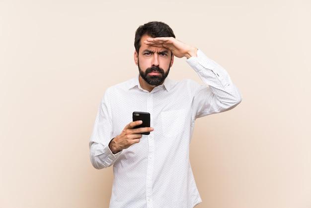 Joven con barba sosteniendo un móvil mirando lejos con la mano para mirar algo
