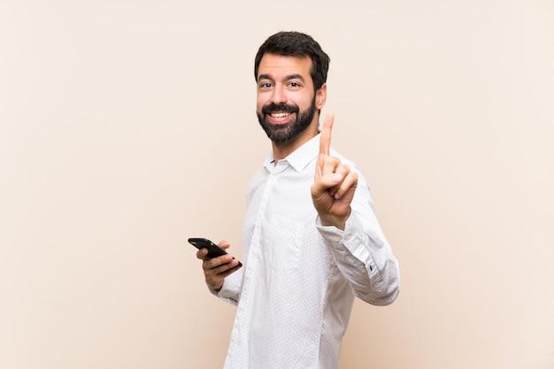 Joven con barba sosteniendo un móvil mostrando y levantando un dedo