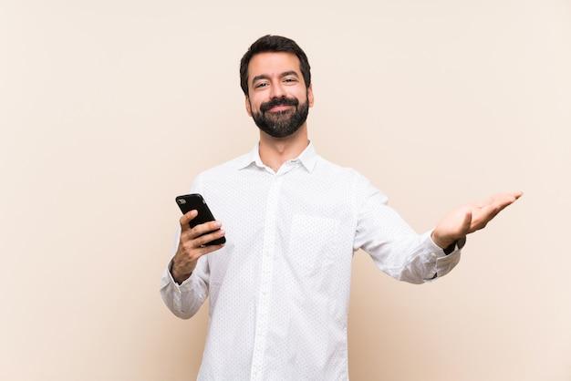 Joven con barba sosteniendo un móvil presentando e invitando a venir con la mano