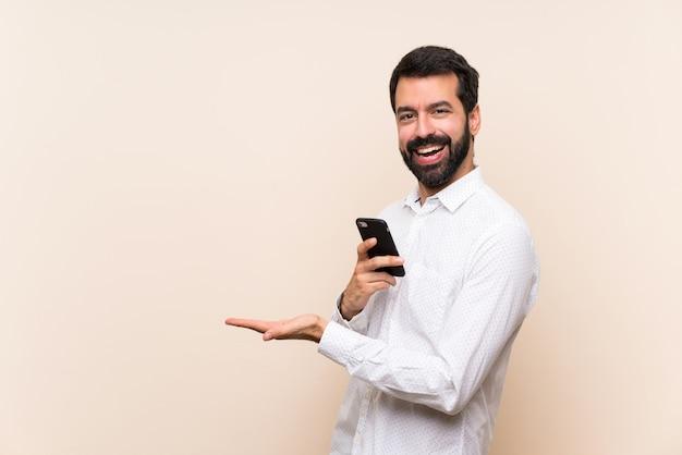 Joven con barba sosteniendo un móvil presentando una idea mientras mira sonriente hacia