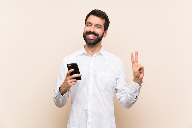 Joven con barba sosteniendo un móvil que muestra el signo de la victoria con ambas manos