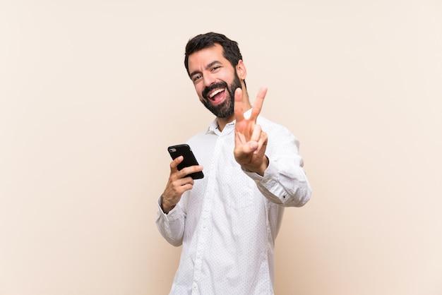 Joven con barba sosteniendo un móvil sonriendo y mostrando el signo de la victoria
