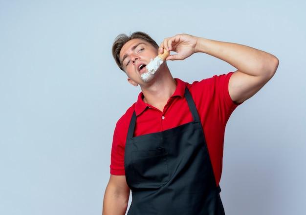 Joven barbero rubio confiado en uniforme mancha espuma de afeitar en la cara mirando al lado aislado en el espacio en blanco con espacio de copia