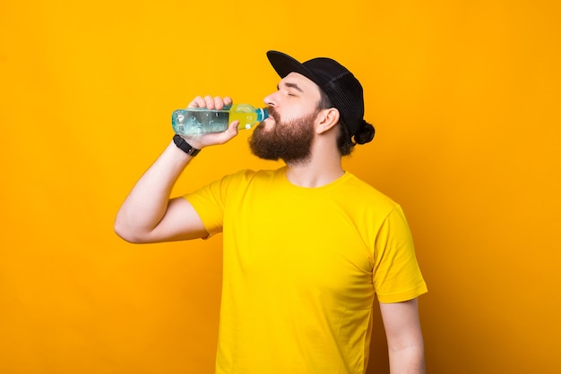 Joven, barbudo, agua potable, en, amarillo