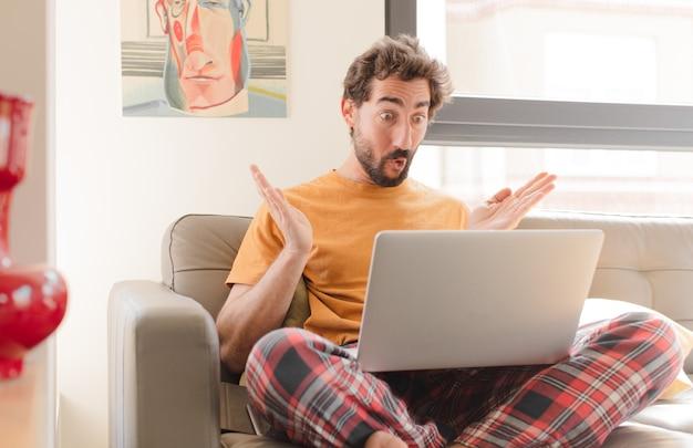 Joven barbudo con la boca abierta y asombrado, sorprendido y asombrado con una increíble sorpresa y sentado con una computadora portátil