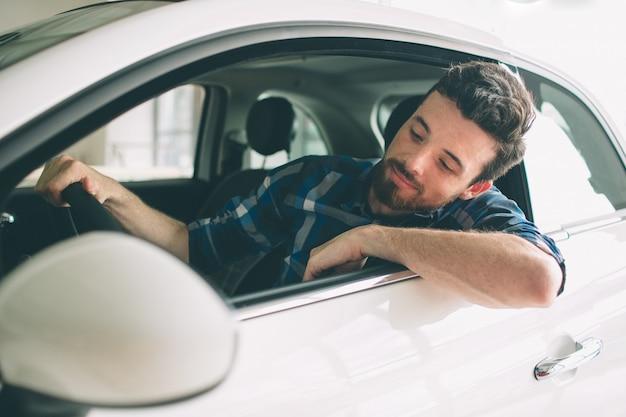Joven barbudo de cabello oscuro examinando el coche en el concesionario y haciendo su elección