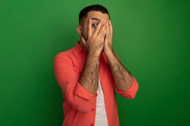 Joven barbudo en camisa naranja que cubre la cara con las palmas de las manos mirando a través de los dedos teniendo miedo de pie sobre la pared verde