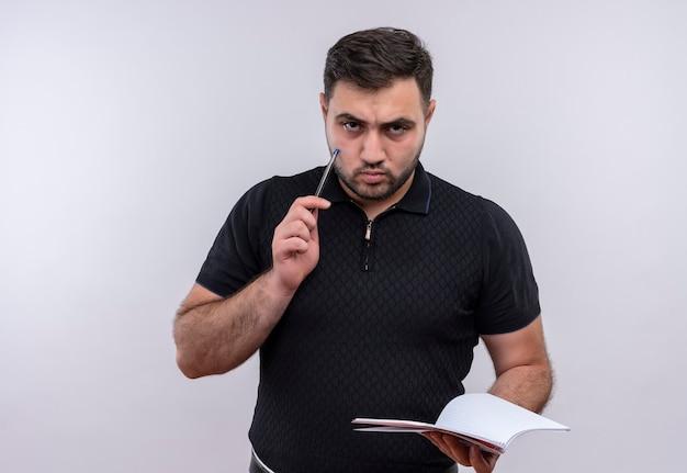 Joven barbudo en camisa negra con cuaderno y bolígrafo mirando a cámara con ceño fruncido