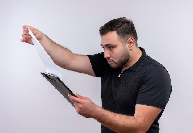 Joven barbudo con camisa negra mirando páginas en blanco en el portapapeles con expresión confusa