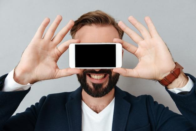 Joven barbudo cara cubierta con teléfono inteligente con pantalla en blanco