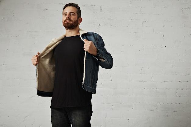 Joven barbudo en chaqueta de mezclilla con forro de piel de oveja muestra su pecho con camisa henley negra sin etiqueta de manga larga, aislado en la pared de ladrillo blanco en el club