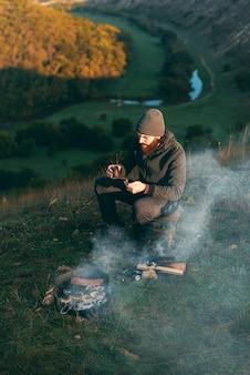 Joven barbudo en una colina está sentado cerca de una parrilla con un café