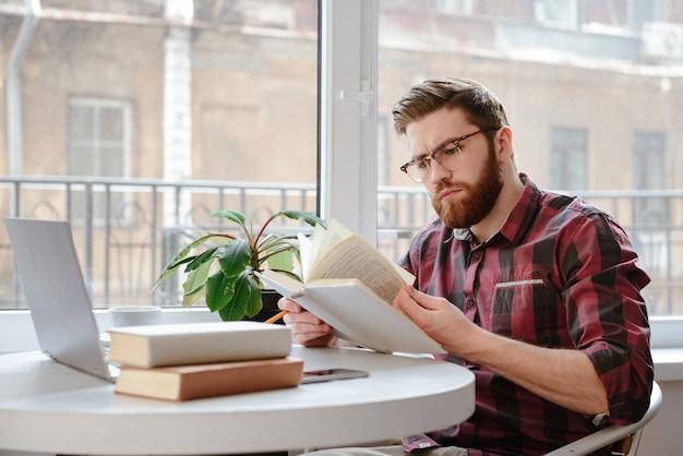 Joven barbudo concentrado leyendo libros mientras usa la computadora portátil