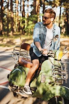 Joven barbudo concentrado sentado en scooter al aire libre