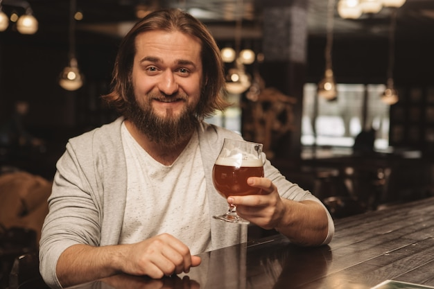 Joven barbudo disfrutando bebiendo cerveza en el pub