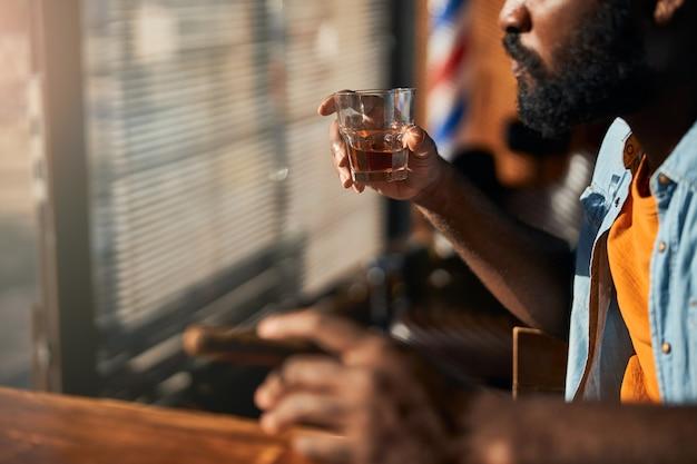 Joven barbudo fumando cigarros y bebiendo whisky