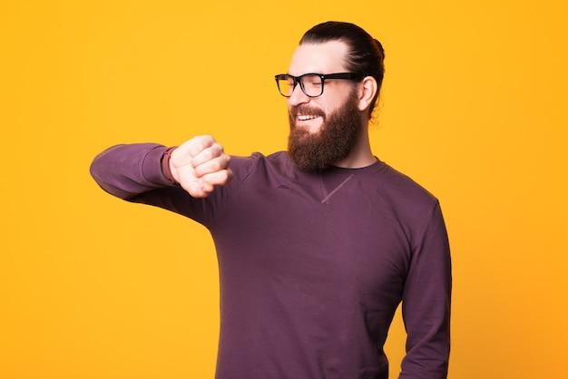 Joven barbudo con gafas está sonriendo y mirando su reloj
