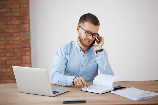 Joven barbudo gerente caucásico en gafas y camisa azul hablando con el cliente por teléfono, discutiendo los detalles del pedido