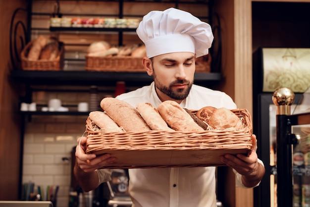 Joven barbudo en gorra blanca de pie en panadería