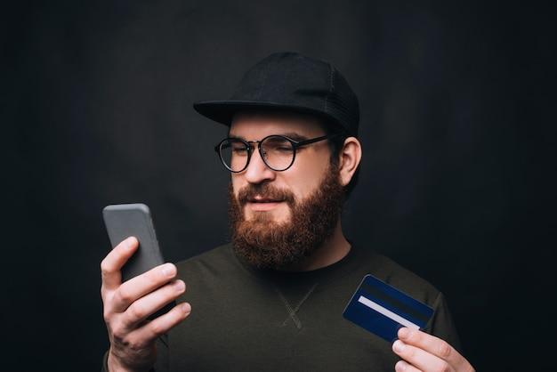 Joven barbudo haciendo pedidos en línea en su teléfono pagando con tarjeta.
