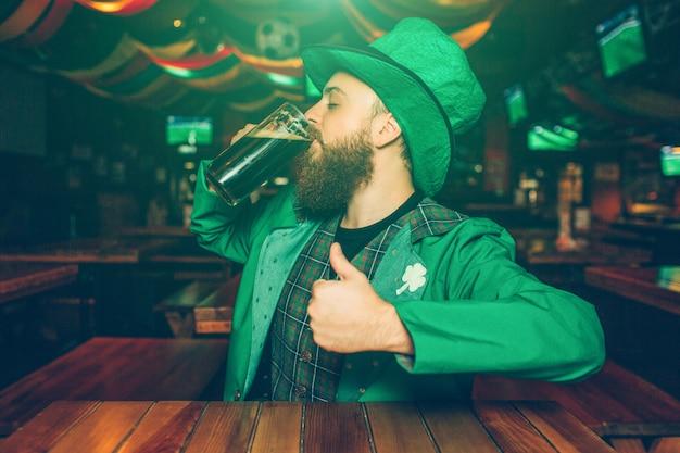 Joven barbudo hombre sentado a la mesa en el pub. bebe cerveza oscura de myg. el tipo usa el traje de san patricio.