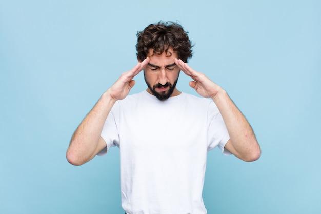 Joven barbudo loco que parece concentrado, pensativo e inspirado, haciendo una lluvia de ideas e imaginando con las manos en la frente en la pared plana