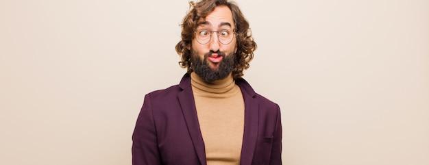 Joven barbudo loco que parece tonto y divertido con una expresión tonta con los ojos cruzados, bromeando y bromeando contra el color plano