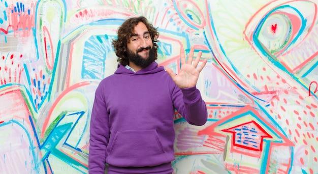 Joven barbudo loco sonriendo y mirando amigable, mostrando el número cinco o quinto con la mano hacia adelante, contando hacia atrás en la pared de graffiti