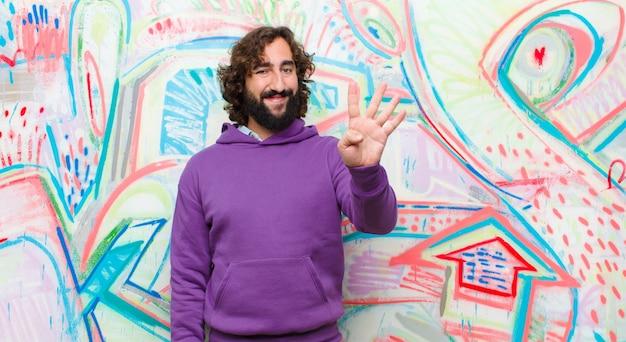 Joven barbudo loco sonriendo y mirando amigable, mostrando el número cuatro o cuarto con la mano hacia adelante, contando en la pared de graffiti