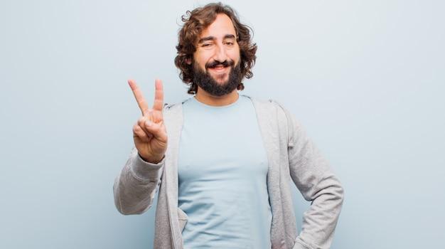 Joven barbudo loco sonriendo y mirando amigable, mostrando el número dos o segundo con la mano hacia adelante, contando hacia atrás contra la pared de color plano