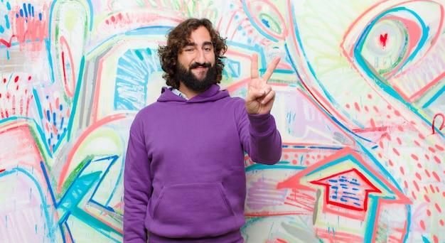 Joven barbudo loco sonriendo y mirando amigable, mostrando el número dos o segundo con la mano hacia adelante, contando en contra del graffiti
