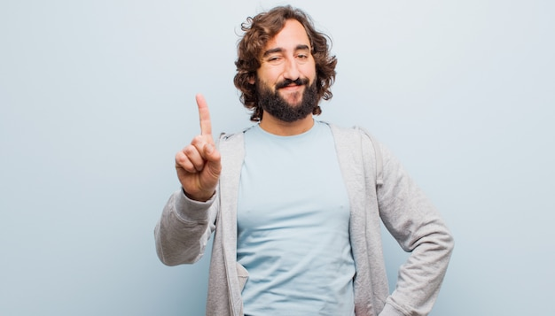 Joven barbudo loco sonriendo y mirando amigable, mostrando el número uno o primero con la mano hacia adelante, contando hacia atrás contra la pared de color plano