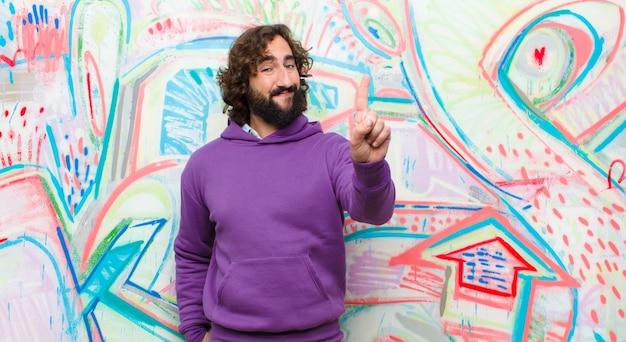 Joven barbudo loco sonriendo y mirando amigable, mostrando el número uno o el primero con la mano hacia adelante, contando en contra del graffiti