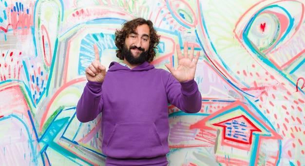 Joven barbudo loco sonriendo y mirando amigable, mostrando el número seis o sexto con la mano hacia adelante, contando en la pared de graffiti