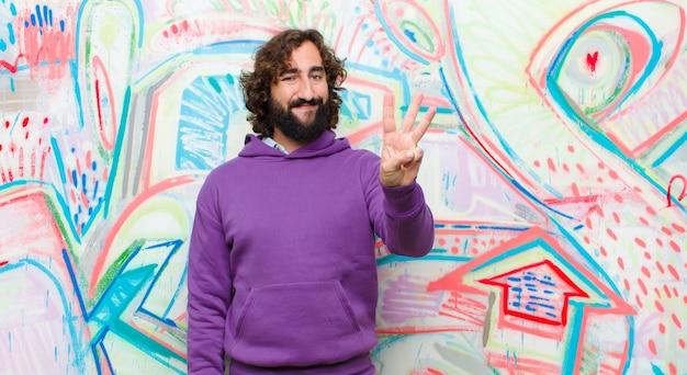 Joven barbudo loco sonriendo y mirando amigable, mostrando el número tres o tercero con la mano hacia adelante, contando en contra del graffiti