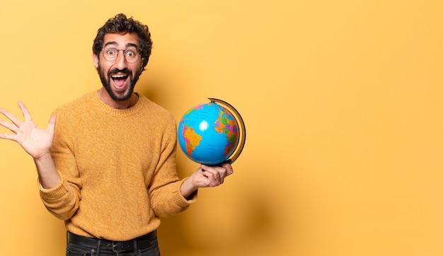 Joven barbudo loco sosteniendo un mapa del globo terráqueo