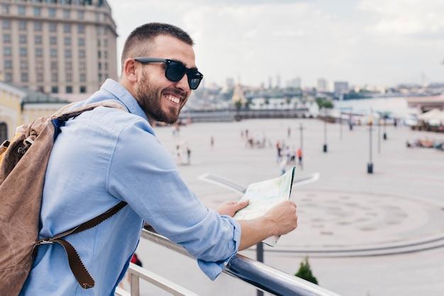 Joven barbudo con mochila y sosteniendo mapa de pie cerca de la barandilla