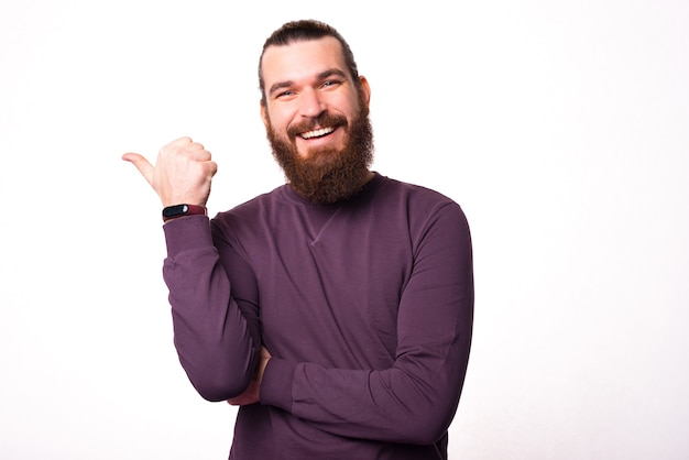 Joven barbudo está mostrando un pulgar hacia arriba y sonriendo a la cámara