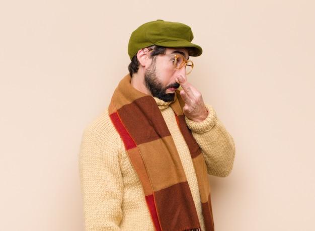Joven barbudo que se siente disgustado, se tapa la nariz para evitar oler un hedor desagradable y desagradable