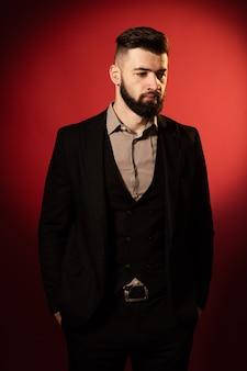 Joven barbudo serio en traje negro sobre fondo rojo.