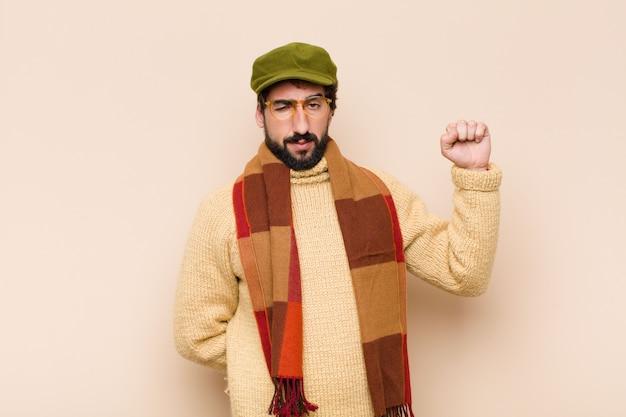 Un joven barbudo se siente serio, fuerte y rebelde, levanta el puño, protesta o lucha por la revolución.