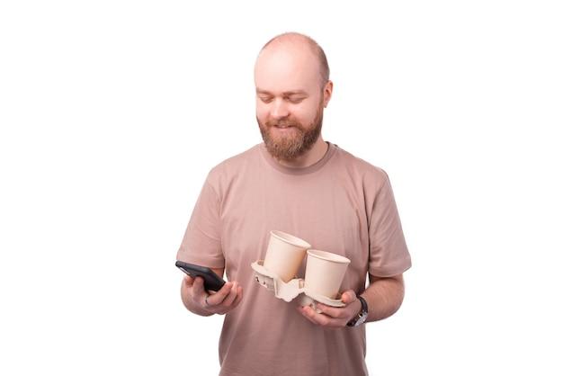 Joven barbudo sosteniendo dos tazas de café y usando un teléfono inteligente en blanco