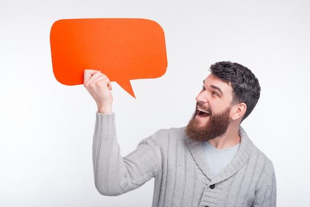 Joven barbudo sostiene una burbuja de discurso naranja, mirando y sonriendo. espacio para tu texto.